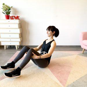 Lächelnde Frau auf dem Boden sitzend