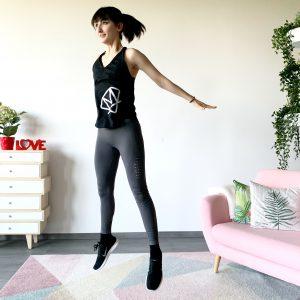 Springende trainierte Frau die lächelt