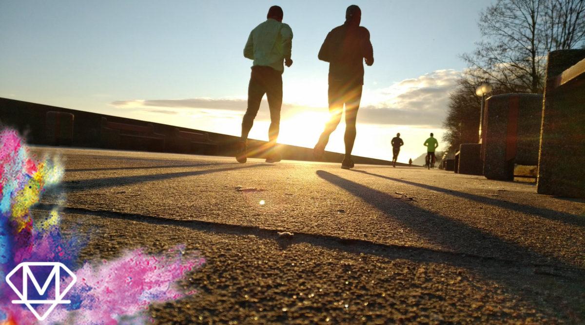 Leute die in den Sonnenuntergang joggen
